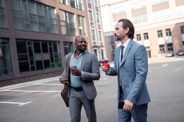 A piedi in ufficio. partner commerciali in possesso di caffè da asporto che camminano insieme in ufficio al mattino