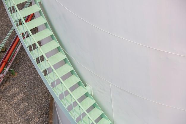 Percorrendo la scalinata verde del serbatoio di stoccaggio chimico.