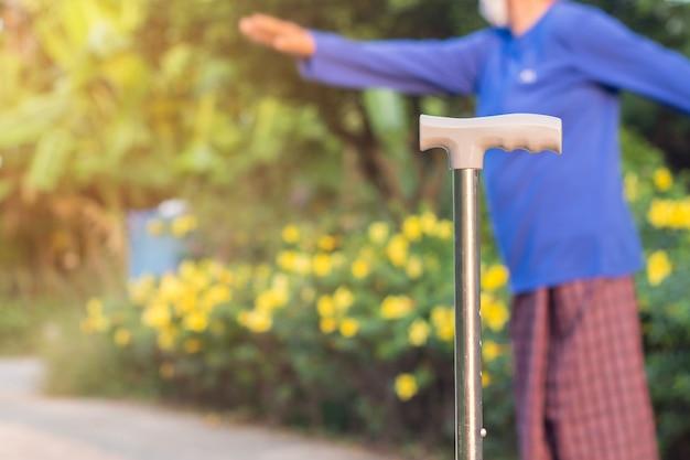 Bastone da passeggio che pone sulla via di mattina sfondo, bastone personale tre gambe