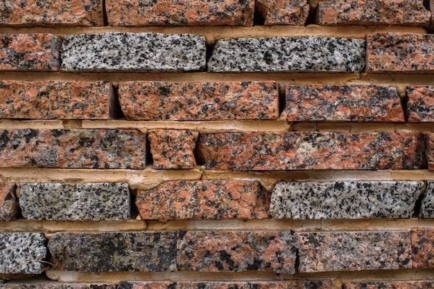 Un bel muro di pietra sulla strada. sfondo. struttura.