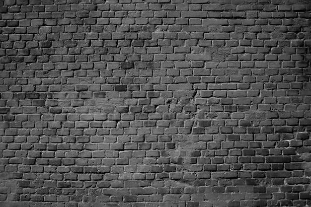 Muro di una casa di mattoni. astratto sfondo nero. trama di mattoni neri. superficie della parete ruvida scura.