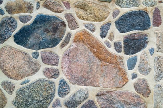 Il muro è in pietra naturale e cemento. frammento di un muro di pietra colorato e strutturato. luminoso