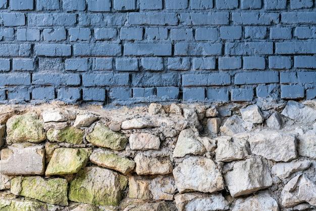 Il muro è in pietra e mattoni. facciata di un edificio cittadino. vernice blu sul muro.