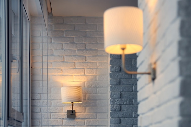 Lampada da parete in moderno appartamento loft. applique da parete sul muro di mattoni bianchi. luci gialle in ombra