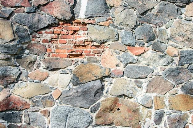 Muro di grandi pietre naturali con un pezzo di mattoni, sfondo naturale.
