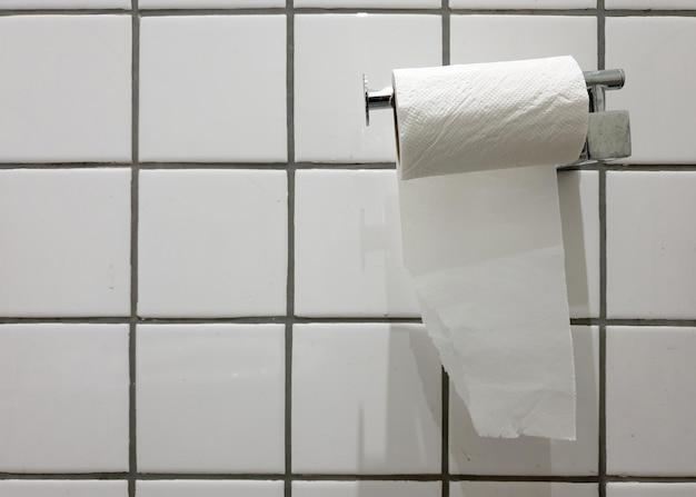 Fissare a parete la carta velina sulla parete piastrellata della toilette
