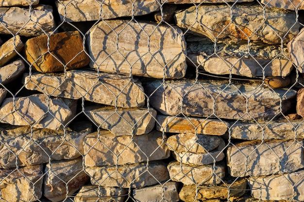 Un muro di pietre naturali dietro una rete metallica. protezione contro i fanghi. foto di alta qualità