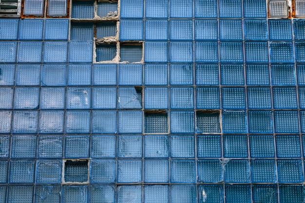 Parete di vecchie piastrelle rotte di vetro blu in un edificio. costruzione astratta.