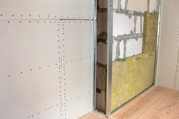 Parete di una stanza in ristrutturazione con isolamento in lana di roccia minerale e telaio metallico predisposto per lastre di cartongesso.