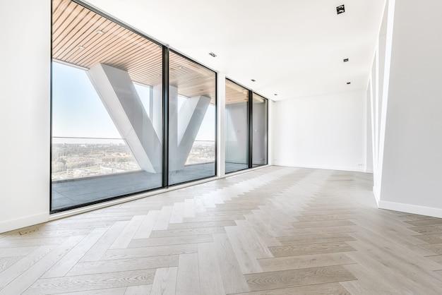 Finestre a parete con pilastro triangolare che guarda il paesaggio urbano da lussuoso attico con pavimento in parquet