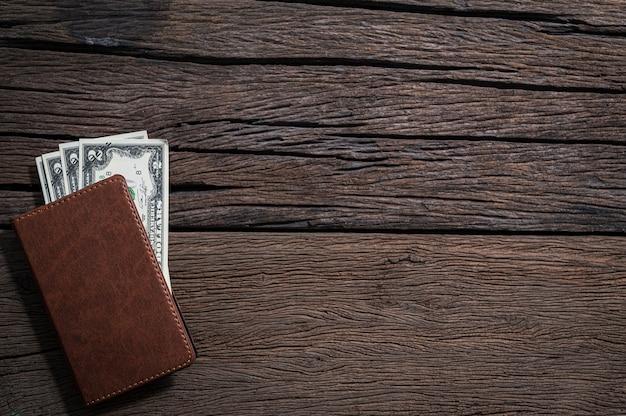 Portafoglio e banconote sono posizionati sul tavolo, vista dall'alto