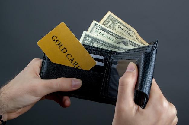 Portafoglio nelle mani di un uomo su un muro grigio credito oro carta soldi dollari