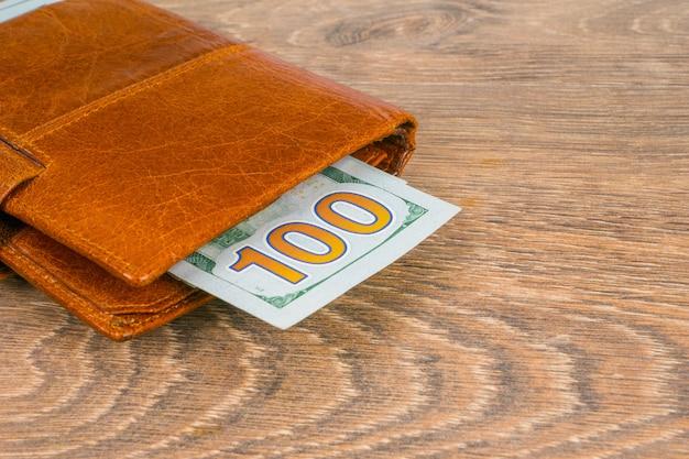 Portafoglio con banconote in dollari sul tavolo