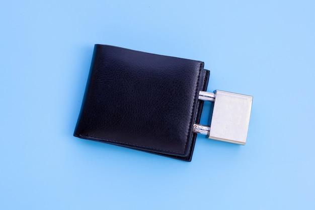 Portafoglio con lucchetto sulla parete blu. copia spazio
