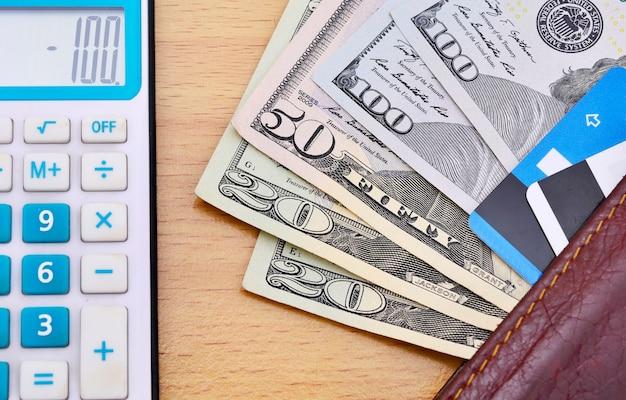 Portafoglio con calcolatrice di dollari americani e carte di credito sul tavolo