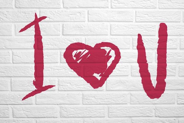 Carta da parati con testo scritto a mano. muro di mattoni bianchi con la scritta ti amo