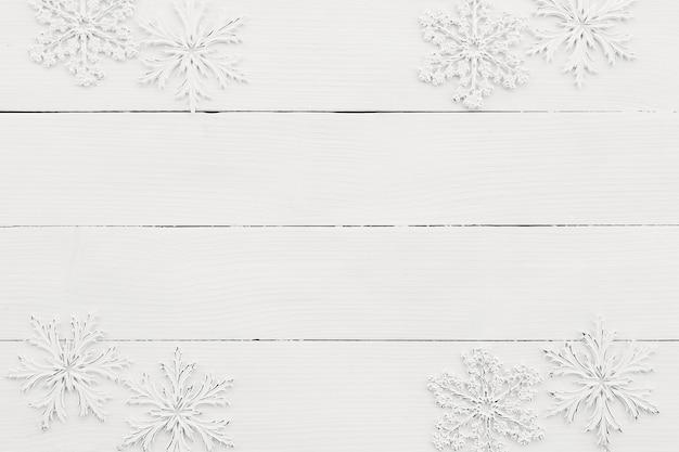 Carta da parati con fiocchi di neve bianchi su fondo di legno bianco.