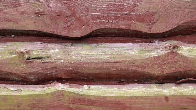 Pareti di vecchie tavole dipinte di marrone, pannelli sovrapposti l'uno all'altro come sfondo. fondo di legno astratto. la trama della recinzione da tavole orizzontali non tagliate. copia spazio, primo piano.