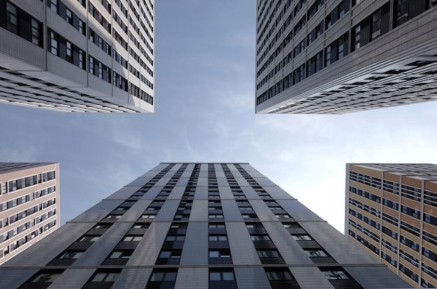 Pareti degli edifici del grattacielo della città moderna con molte finestre nel cluster di affari, vista dal basso in giornata di sole