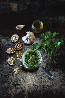 Pesto di noci con prezzemolo. salsa di pesto fatta in casa in un barattolo. vista dall'alto. pesto vegano con noci e prezzemolo.