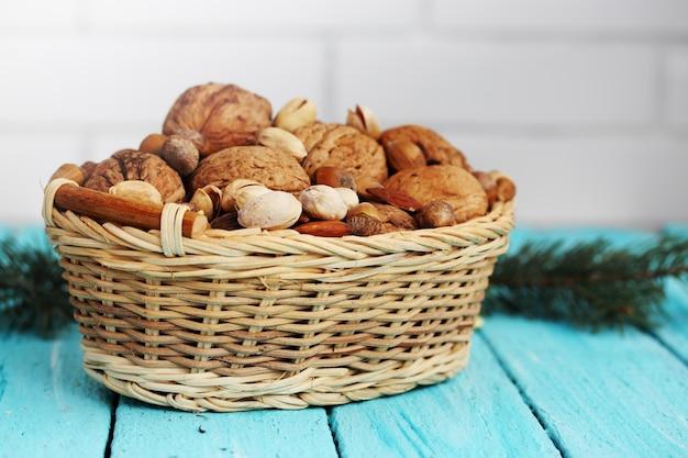 Noci, mandorle, pistacchi in un cesto di vimini