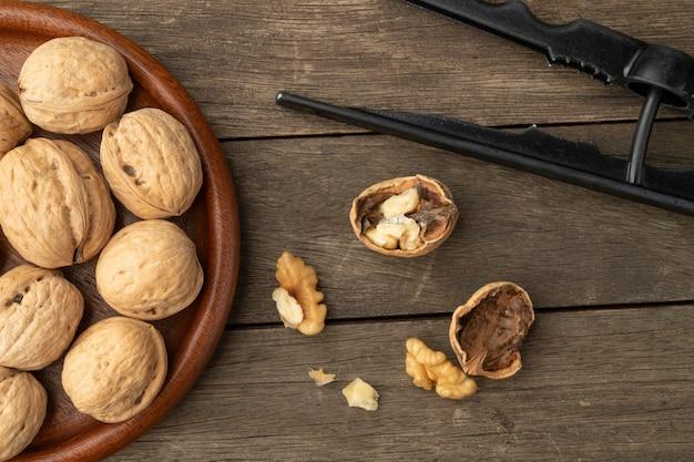 Noci, cracker di noci e noci incrinate sul tavolo di legno.