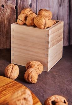 Noci in una scatola di legno, intere e tritate finemente, accanto al ripieno e ai gusci su un piano di legno