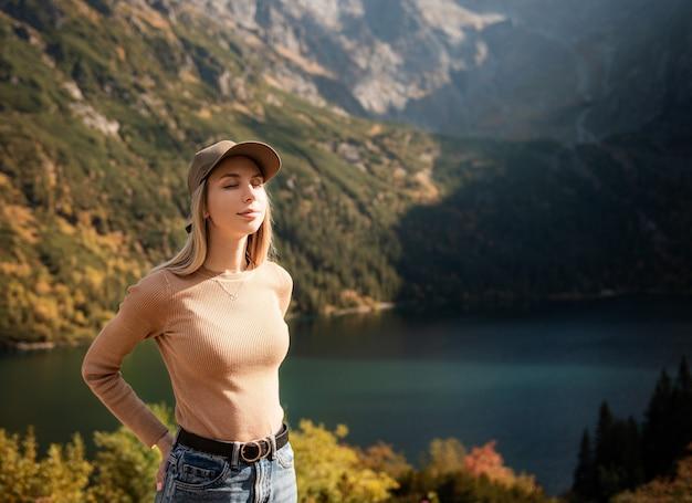 Wanderlust e concetto di viaggio. ragazza alla moda viaggiatrice in berretto guardando le montagne, esplorando i boschi. giovane donna che viaggia nel lago nella foresta. lago di montagna vicino a morskie oko, zakopane