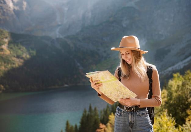 Wanderlust e concetto di viaggio. ragazza viaggiatrice alla moda con cappello guardando la mappa, esplorando i boschi. giovane oman con zaino in viaggio nel lago nella foresta.