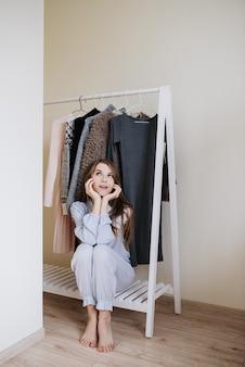 Guardaroba di una giovane ragazza. abiti appesi. scelta della farina cosa vestire? una ragazza in pigiama non sa cosa indossare.