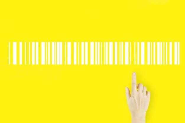 Magazzino e concetto di logistica. la mano della giovane donna che indica il dito con il cartellino del prezzo del codice a barre dell'ologramma su fondo giallo. concetto di produzione logistica di inventario.