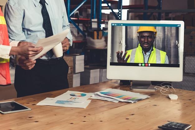Il personale del magazzino parla in videochiamata allo schermo del computer nel magazzino di stoccaggio