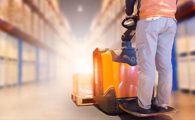 Magazziniere che guida il carrello elevatore elettrico pallet jack scarico pacchi scatole magazzino di stoccaggio