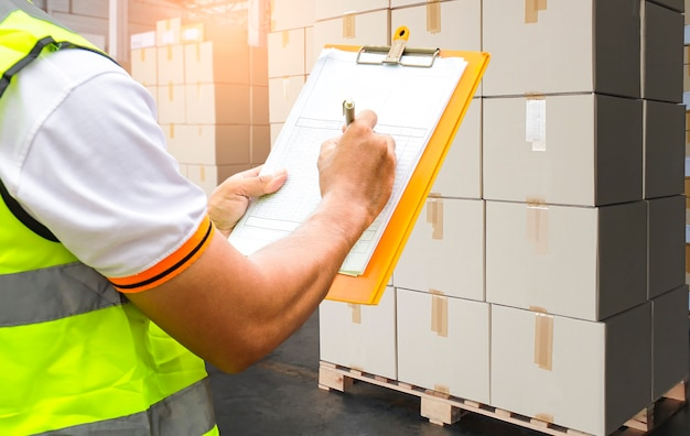 Magazzino lavoratore tenendo appunti il suo facendo la gestione dell'inventario scatole di carico controllo delle scorte spedizione del carico