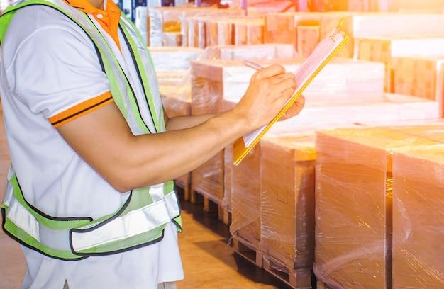Magazziniere che tiene gli appunti mentre sta facendo il controllo della gestione dell'inventario scatole di spedizione del carico delle scorte