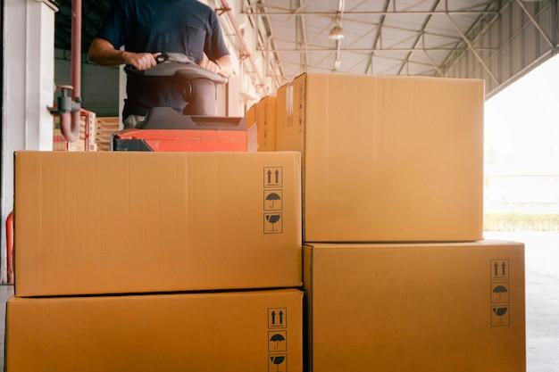 Addetto al magazzino che carica scatole di pacchi nelle scatole di spedizione del magazzino