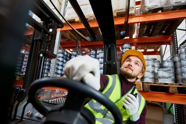 Merci commoventi del lavoratore del magazzino facendo uso del carrello elevatore