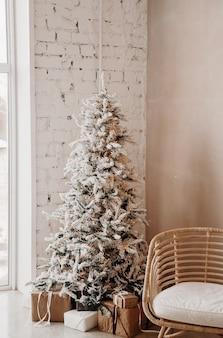 Caldo, accogliente, bellissimo design moderno della camera in delicati colori chiari decorati con albero di natale.