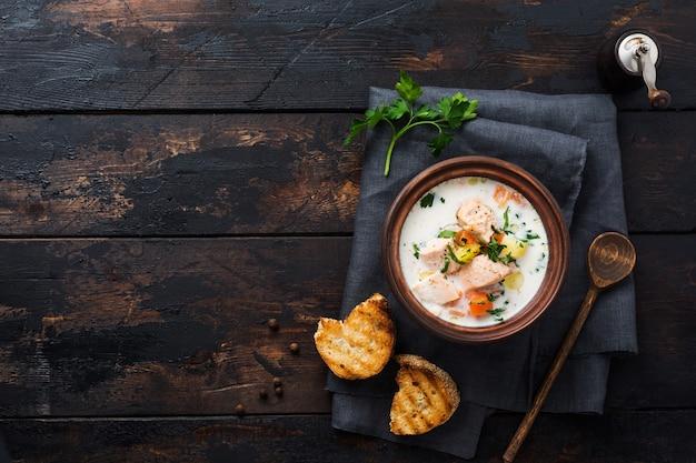 Zuppa cremosa finlandese calda con salmone e verdure in una vecchia ciotola di ceramica