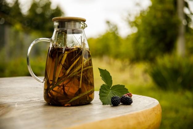 Teiera di vetro calda, foglie di tè verde e citronella sulla scrivania in legno al mattino.
