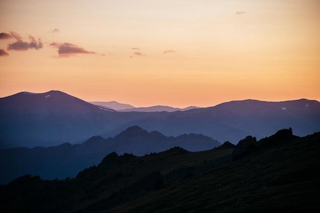 Caldo gradiente del cielo all'alba sopra strati di sagome di montagne e rocce.