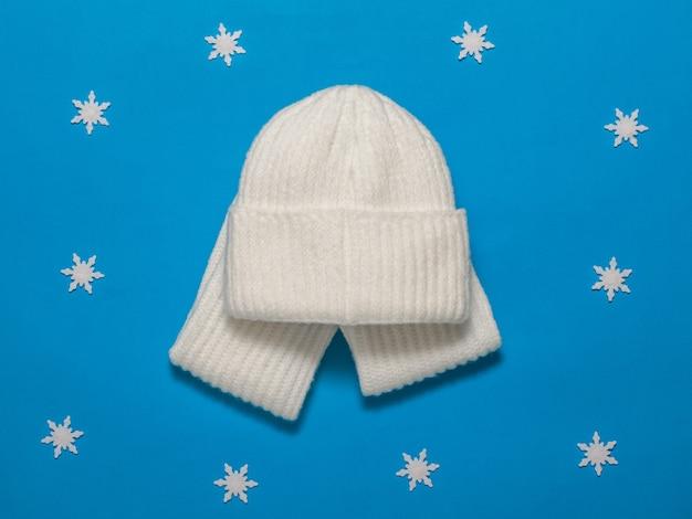 Caldo cappello lavorato a maglia e sciarpa con fiocchi di neve. accessori invernali alla moda.