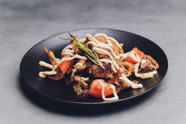 Insalata tiepida di lattuga con fegatini di pollo, funghi fritti, olio d'oliva, condimenti e aceto balsamico. deliziosa cena gourmet. messa a fuoco selettiva.