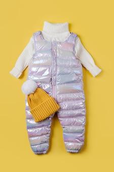 Pantaloni caldi e maglione bianco su sfondo giallo. set di vestiti per bambini per l'inverno. vestito alla moda per bambini.