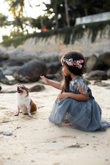 Fotografia calda di un cane carino e una ragazza preadolescente in abito con ghirlanda che stanno giocando sulla costa in thailnd.