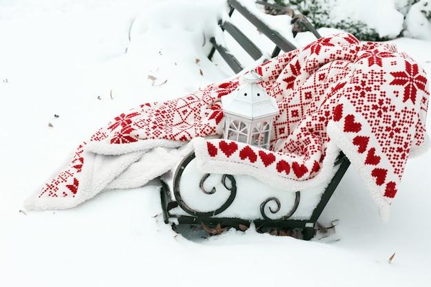 Caldo plaid sulla panchina nel parco in inverno