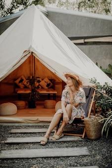 Caldo ritratto di una viaggiatrice con cappello di paglia che si siede su una sedia e distoglie lo sguardo sorridente in thailandia.
