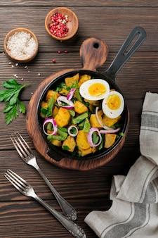 Insalata tiepida di patate con fagiolini, pepe, prezzemolo, uova e cipolla rossa in padella sul vecchio tavolo di legno. messa a fuoco selettiva. vista dall'alto. copia spazio.