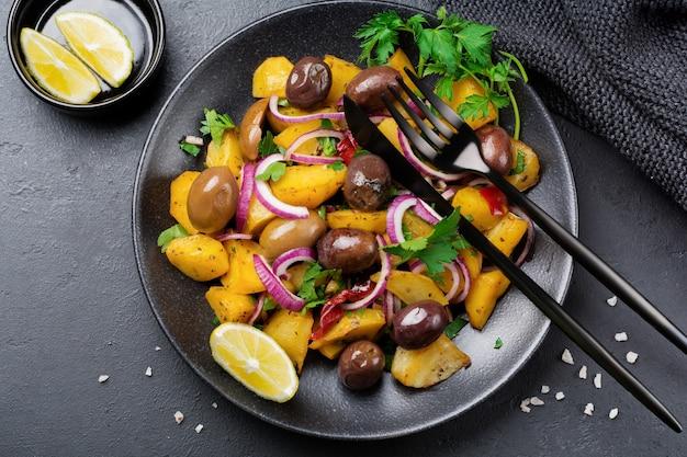 Insalata tiepida di patate con olive, pepe, prezzemolo e cipolla rossa su piatto in ceramica nera su superficie di cemento scuro