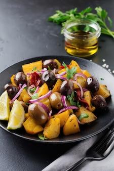 Insalata calda di patate con olive, pepe, prezzemolo e cipolla rossa su piatto in ceramica nera
